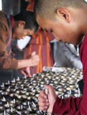 Monks lighting votives