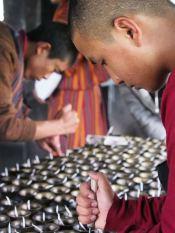 Monks lighting votives